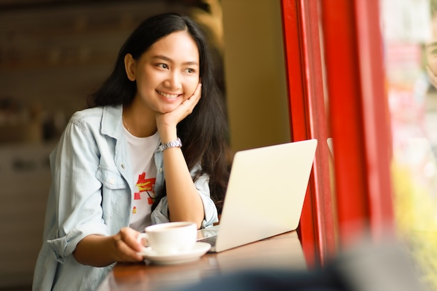 アジアの女性のラップトップを使用してカフェでコーヒーを飲む