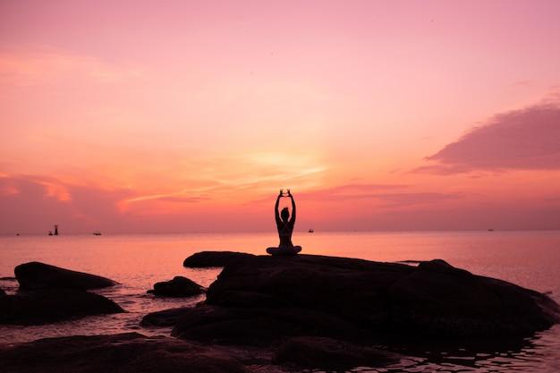 アジアの女の子がビーチでヨガを練習します。日の出の朝の日
