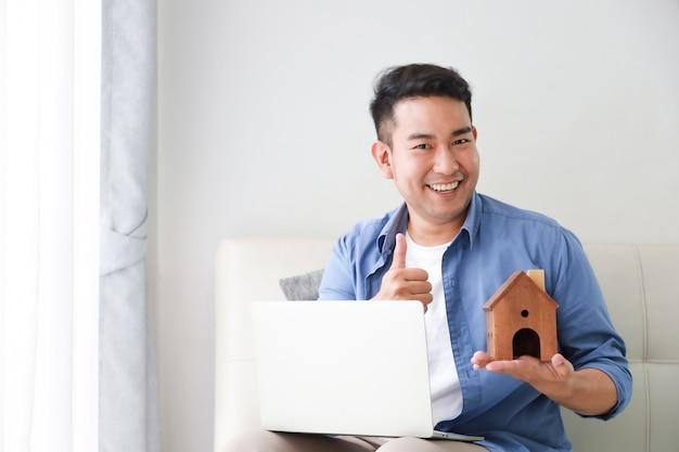 ラップトップコンピューターとリビングルームで家の概念のための銀行ローンの小さな家モデルを示す青いシャツを着た若いアジア人