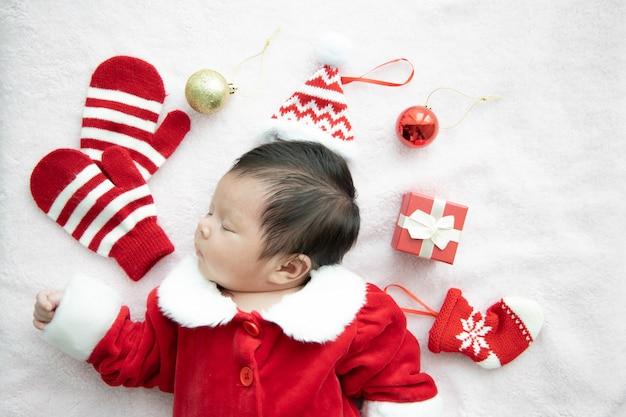赤いボックスプレゼントと赤い帽子で寝ているサンタクロースの制服を着たアジアの赤ちゃん