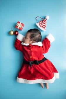 赤いボックスプレゼントと青い背景に赤い帽子で寝ているサンタクロースの制服にアジアの赤ちゃん新生児
