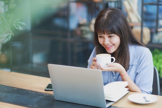 ラップトップを使用して、コーヒーを飲みながら青いシャツを着てアジアの美しい女性