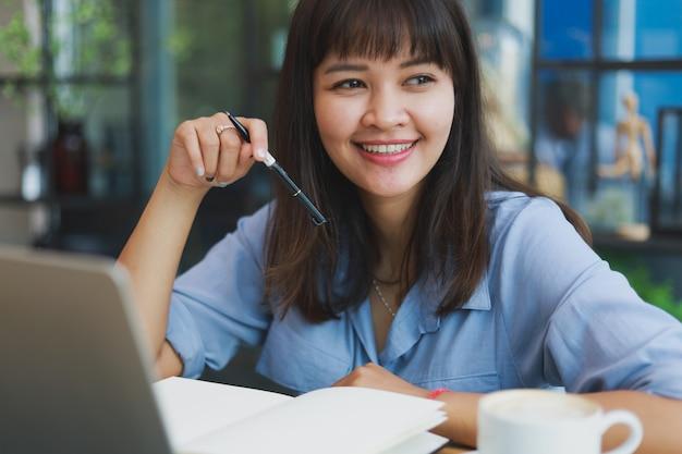 Азиатская красивая женщина в синей рубашке, используя ноутбук и пить кофе