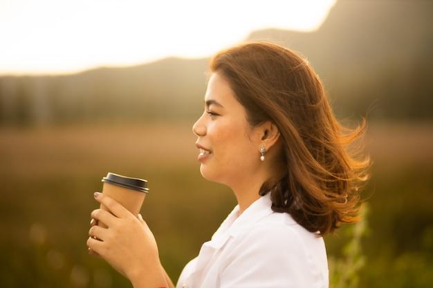 Молодая азиатская женщина в белой рубашке выпивая кофе напольный в временени восхода солнца