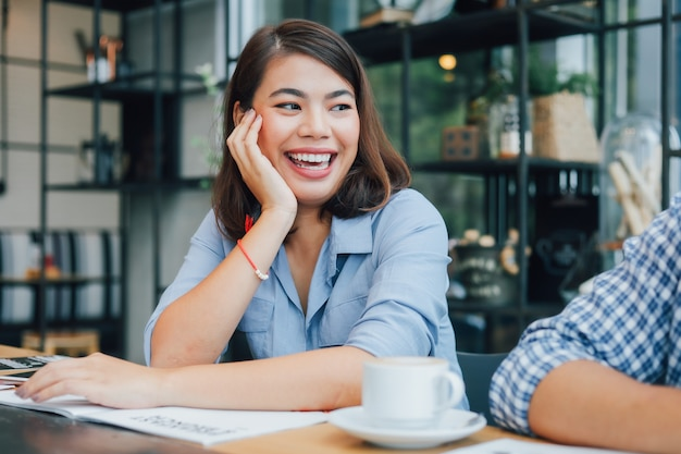 Азиатская женщина в синей рубашке в кафе, пить кофе и разговаривать с дружком улыбкой и счастливым лицом