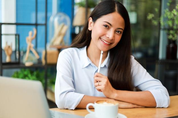 青いシャツを着てアジアの女性とコーヒーショップカフェでコーヒーを飲む