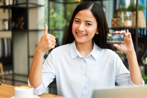 コーヒーショップカフェでオンラインショッピングクレジットカードを使用してアジアの女性