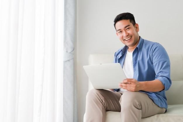 Азиатский красавец работает с ноутбуком в гостиной, счастливые и улыбающиеся лица