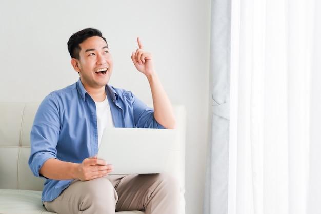 アジアのハンサムな男の幸せなリビングルームでラップトップコンピューターでの作業と笑顔