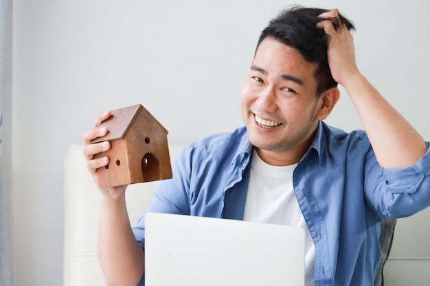 ラップトップコンピューターとリビングルームで家の概念のための銀行ローンの小さな家モデルを示す青いシャツの若いアジア人