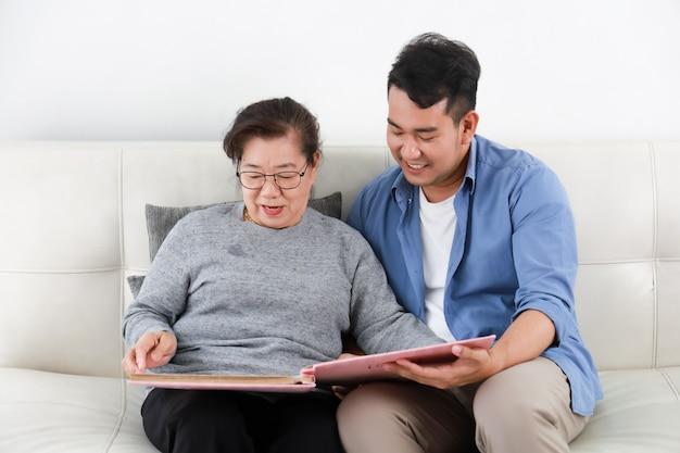 アジアのシニア女性の母親と若い男の息子の写真を探している青いシャツとリビングルームで幸せな笑顔の顔を話して