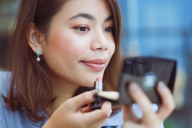 アジアの女性がカフェで口紅で顔を作る