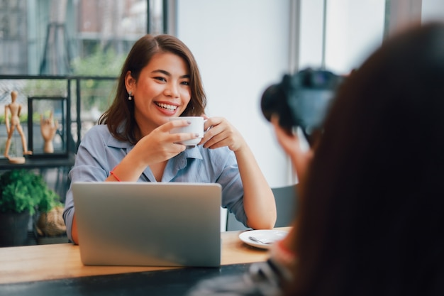コーヒーを飲みながら、ボーイフレンドの笑顔と幸せそうな顔と話しているカフェで青いシャツのアジア女性