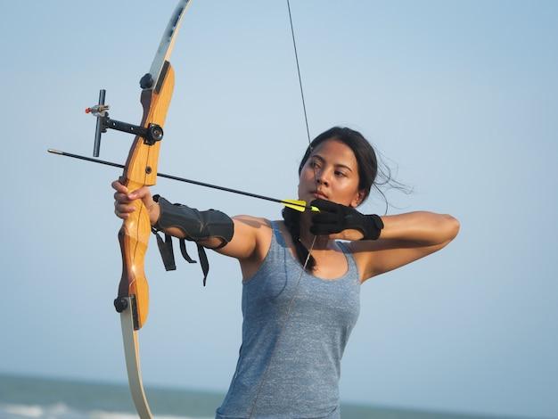 ビーチでの弓の射撃を持つアジアアーチェリー女性