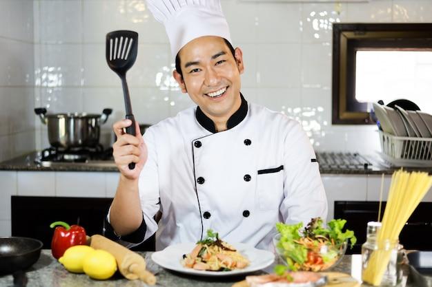 アジアの男性シェフがレストランで料理