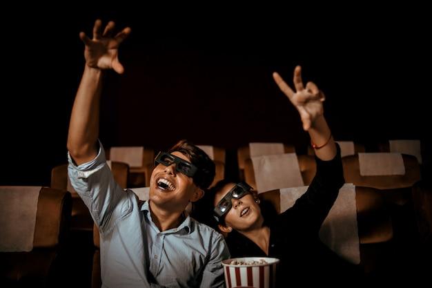 Пара смотрит фильм в театре с попкорном и счастливым лицом