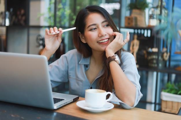 Азиатская женщина работает и пить кофе в кафе с улыбкой портативного компьютера и счастливой работы