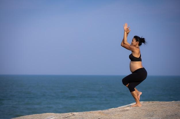 夏のビーチの夕日にアジアの妊娠中の女性のヨガ
