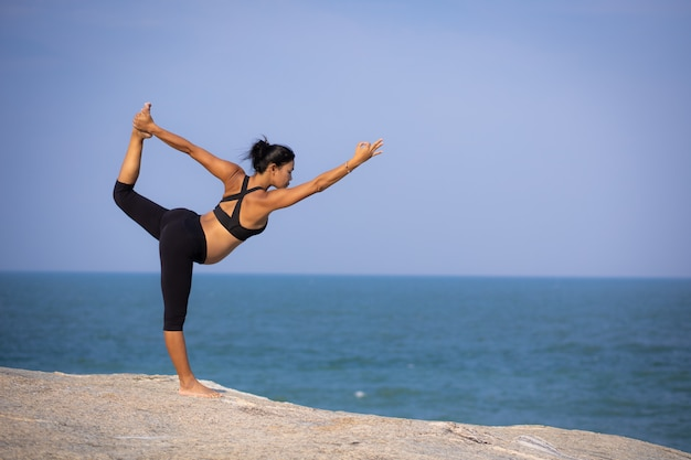 Азиатская йога беременной женщины на пляже закат летнее время