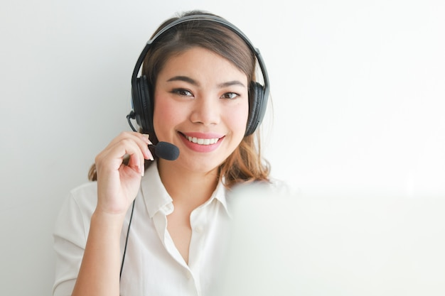 白いシャツのアジアの女性はヘッドフォンで話すし、ラップトップ、笑顔、幸せそうな顔のオペレーターの概念を使用して