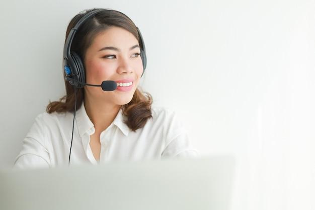 Азиатская женщина на белой рубашке говорит с наушниками и используя концепцию оператора компьтер-книжки, улыбки и счастливого лица