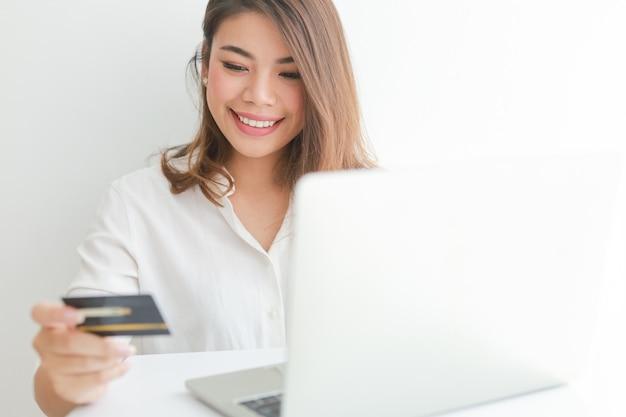 ラップトップコンピューターでオンラインショッピングクレジットカードを使用してアジアの女性、