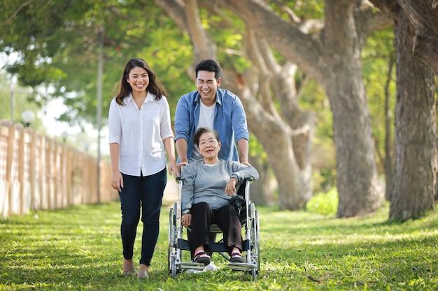 Азиатская старшая женщина сидя на кресло-коляске с стороной счастливой улыбки семьи на зеленом парке