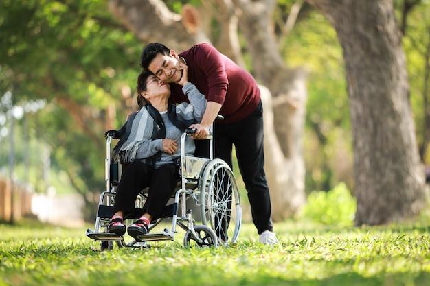 Азиатская старшая женщина сидя на кресло-коляске с ее стороной счастливой улыбки сына на зеленом парке