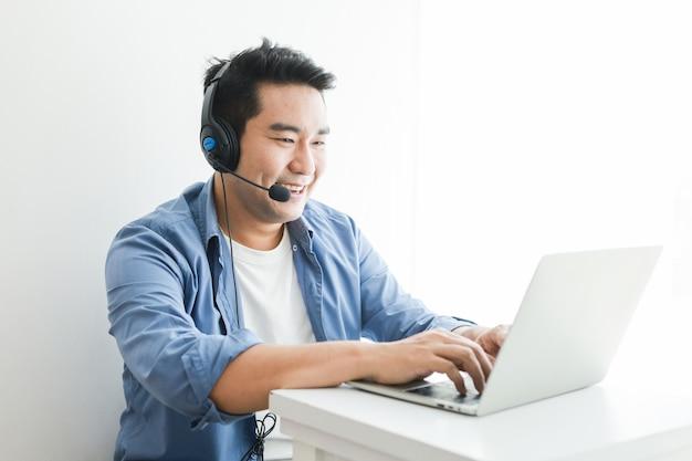 Азиатский красавец в синей рубашке, используя ноутбук с наушниками, говорить улыбкой и счастливым лицом