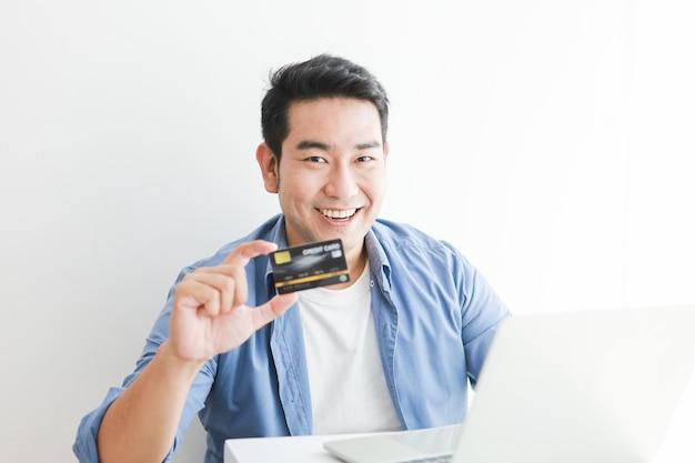 オンラインショッピングのラップトップコンピューターでクレジットカードを使用して青いシャツを着たアジアのハンサムな男