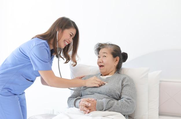 Азиатская старшая старуха на кровати с доктором и ее сыном в больнице