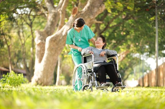 Азиатская старшая женщина сидя на кресло-коляске с женщиной в форме доктора в больнице парка
