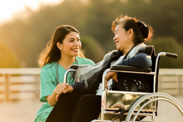 公園の病院で医師の制服を着た女性と車椅子に座っているアジアの年配の女性