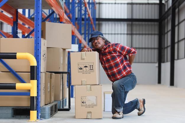 アジア人労働者の男が工場で彼の背中を持ち上げる重い箱を傷つける