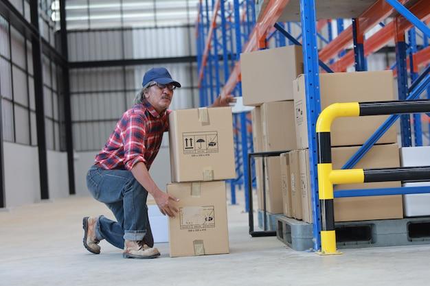 Азиатский рабочий человек поднять тяжелую коробку на заводе
