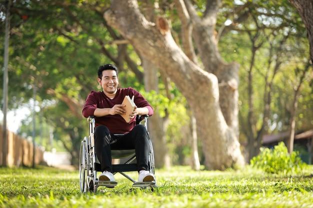 公園の病院で車椅子に座っているアジアの若い男