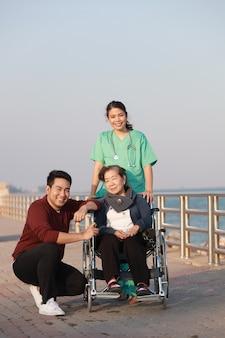 公園の病院で医者の制服を着た女性と車椅子に座っているアジアの年配の女性