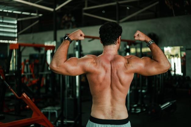 筋肉の強いボディを持つジムボディービルでハンサムな男運動
