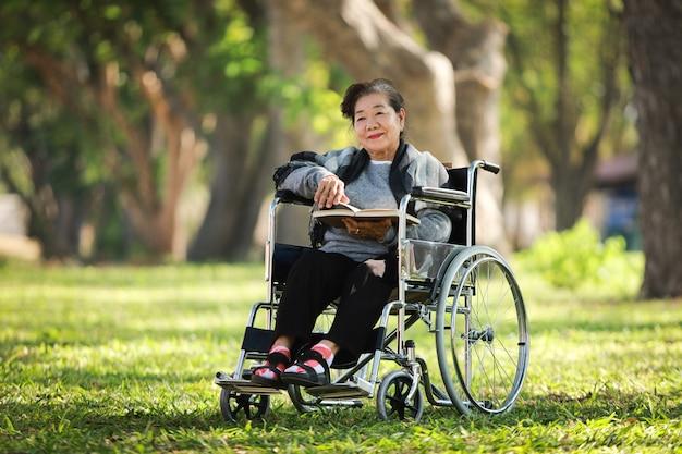 Азиатская старшая женщина сидя на кресло-коляске читая книгу в парке