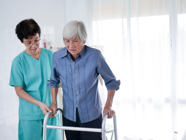 ウォーキングフレームを使用している老人女性を助ける看護師。