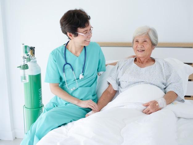 Медсестра заботится о пожилой женщине в больничной палате.