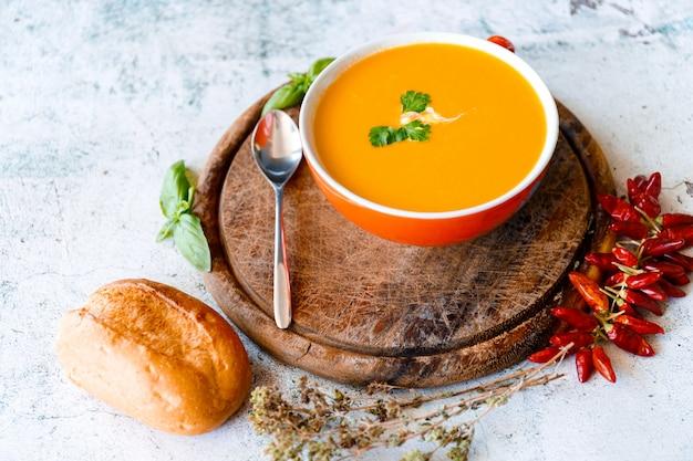 Тарелка острого тыквенного супа, заправленная кокосовым кремом