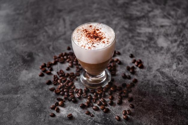 黒い表面にカプチーノのカップ。ローストコーヒー豆、ホットミルク、コーヒー、カカオパウダー、コピースペース