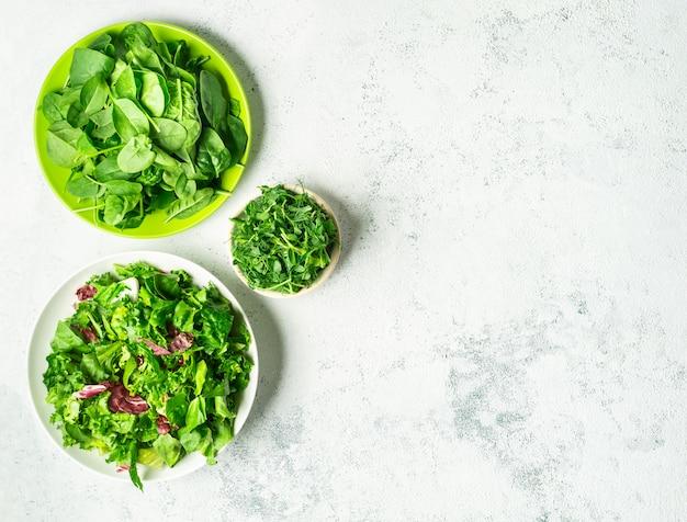 白い背景の上に葉を混ぜた細切りサラダと木のボウル