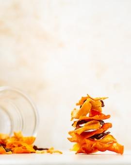 ビートの根、ニンジン、明るい色の背景にパースニップから作られた野菜チップを積み上げ