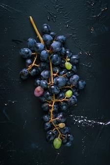 暗い青色の背景に青ブドウの房