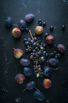暗い青色の背景に青ブドウとイチジクの束