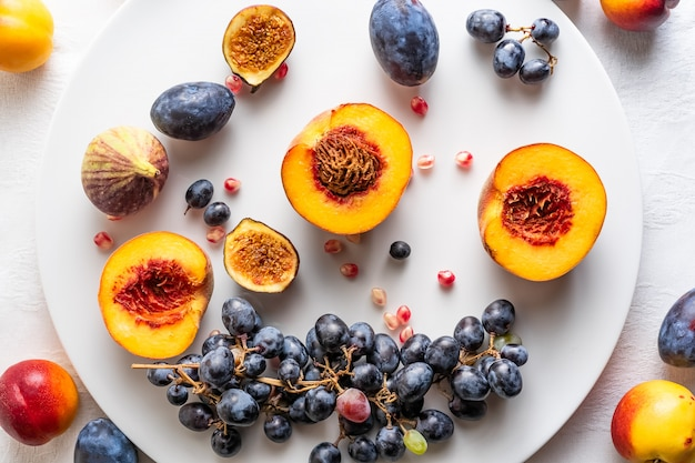 Персики пополам с нектаринами и виноградом на белой тарелке