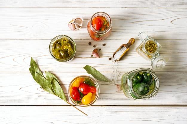 Овощные консервы в стеклянных банках, приготовление ингредиентов на белом фоне деревянные, вид сверху. горизонтальная ориентация.