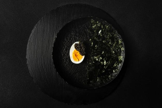 Закуска из осетровой икры, половина вареного яйца, измельченные нори на черной тарелке на черном фоне